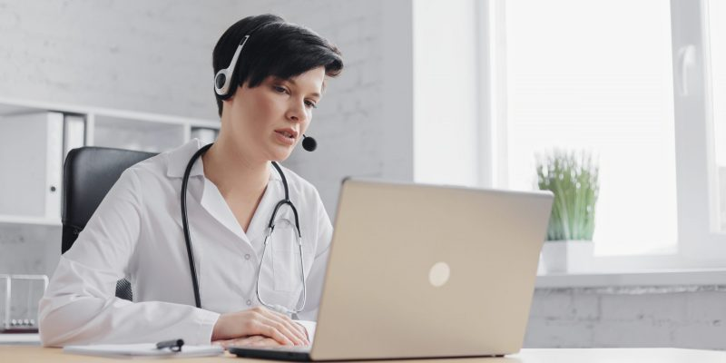 Female doctor consulting patient remote online using headset and web camera on laptop.